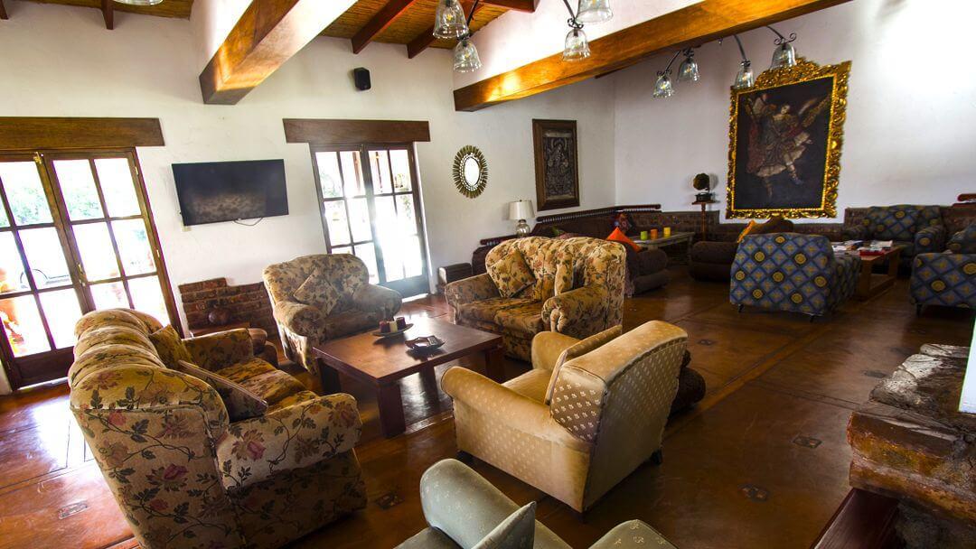 Sala de descanso interior rodeado de pinturas coloniales y mobiliario antiguo.