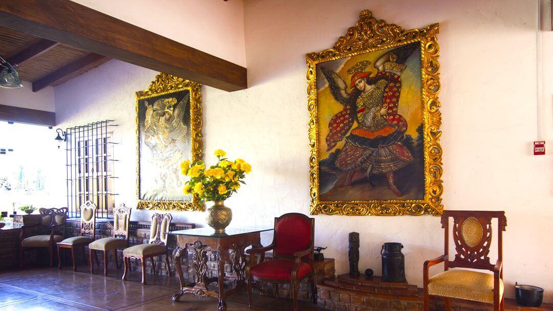 Magníficas pinturas restauradas, sillas y mesas coloniales que puedes apreciar en tu estadía en el hotel.