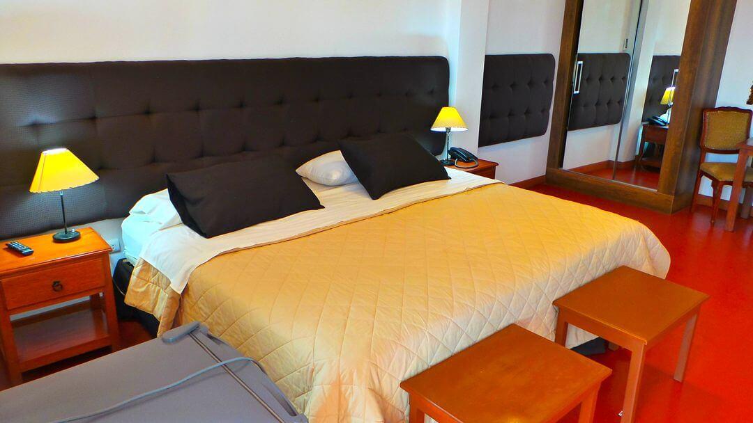 Cama grande y confortable de habitación simple en hotel de Nasca.